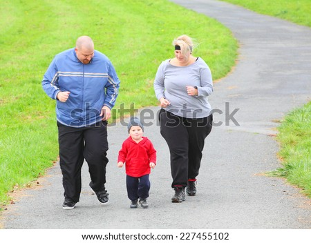 Overweight parents with her son running together. - stock photo