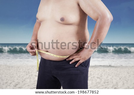 Overweight person measuring his belly  - stock photo