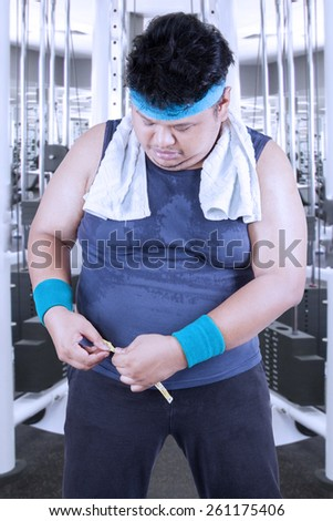 Overweight persong standing in the fitness center while measuring his waistline with a measurement tape - stock photo
