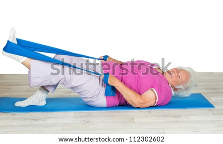 Overweight senior woman full of zest and vitality exercising on a gym mat with her leg raised in the air using a strap for leverage - stock photo