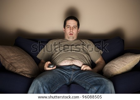 Overweight slob watches TV with belly showing - stock photo