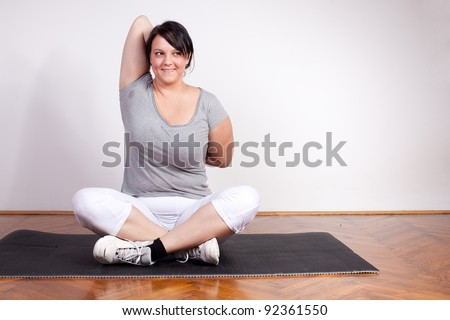 Overweight woman exercising/stretching - stock photo