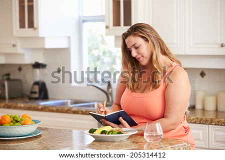 Overweight Woman On Diet Keeping Food Journal - stock photo