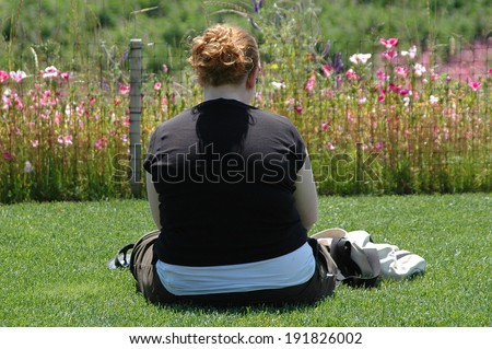 Overweight woman sitting outside alone. - stock photo