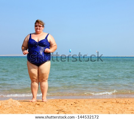 overweight woman standing on beach near sea - stock photo