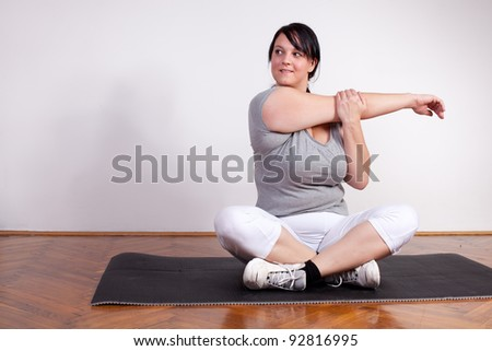Overweight woman stretching at home - stock photo