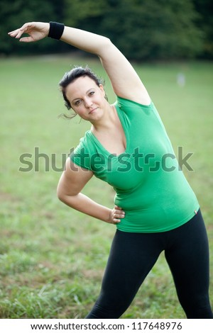 Overweight woman stretching in the park - stock photo