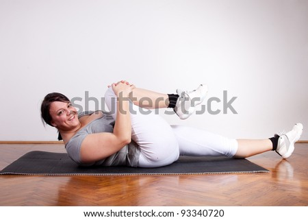 Overweight woman stretching on the floor - stock photo