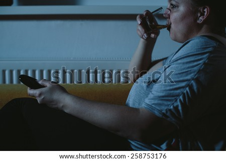 Overweight woman watching TV drinking whiskey - stock photo