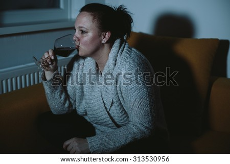 Overweight woman watching TV drinking wine