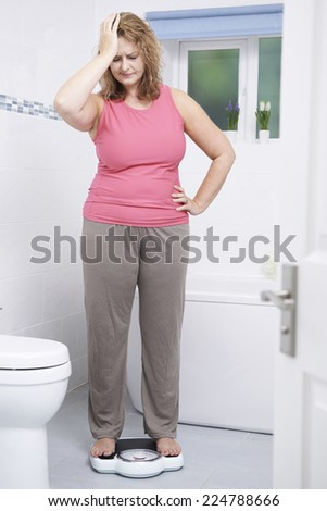 Overweight Woman Weighing Herself On Scales In Bathroom - stock photo