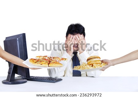 Overweight worker covering his face and refuse to eat fast food, isolated on white background - stock photo