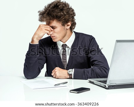 Overwhelmed Businessman dissatisfied with his earnings, gain, benefit, margin / modern businessman at the workplace working with computer on grey background. Depression and crisis concept