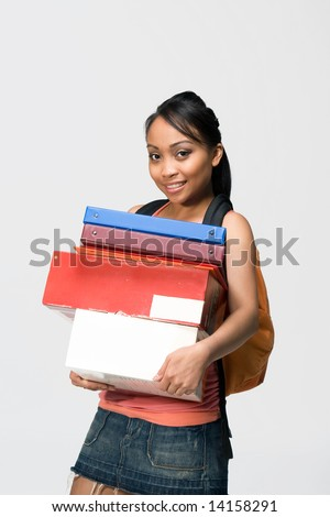 Overwhelmed female student wearing a backpack carries notebooks and papers. Vertically framed photograph. - stock photo