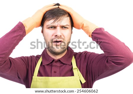Overwhelmed young man with apron and gloves holding hands on head over white - stock photo