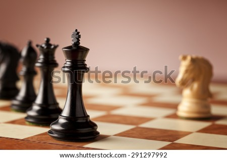 Overwhelming advantage - main black chess pieces facing single white knight on a luxurious traditional chessboard in focus - stock photo