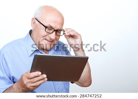 Overwhelming network. Agreeable grandfather touching glasses and holding laptop with his glance down while surfing through the Internet - stock photo