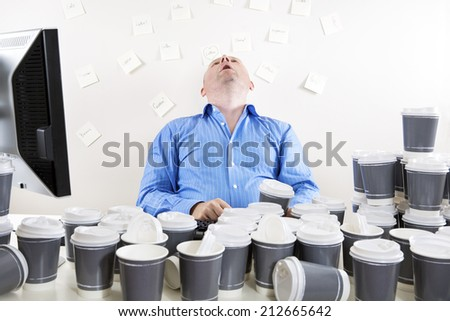 Overworked and exhausted office worker - stock photo