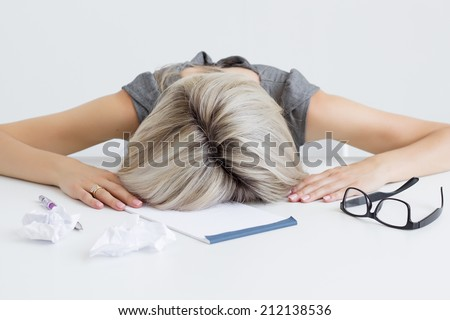 Overworked and tired young woman sleeping on desk - stock photo