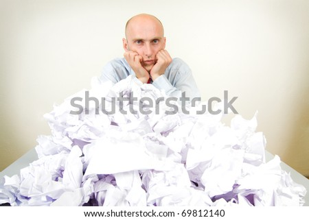 Overworked bald headed male businessman partially buried in paperwork; studio background. - stock photo