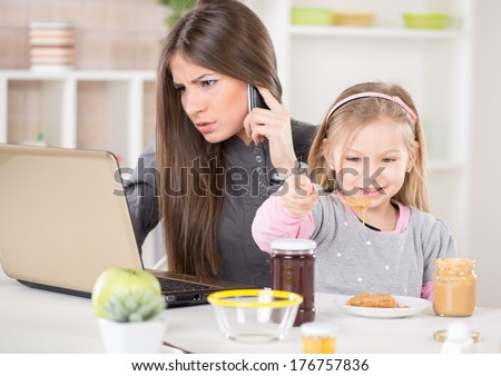 Overworked Business Woman and her little daughter in the morning. Mother read mail and make phone calls before going to work. Daughter smearing peanut butter on bread. - stock photo