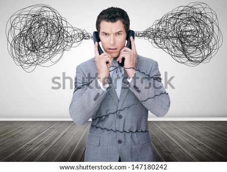Overworked businessman holding two telephones and looking at camera - stock photo