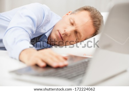 Overworked businessman sleeping. Senior man in formalwear holding hand on laptop keyboard while sleeping in bed   - stock photo