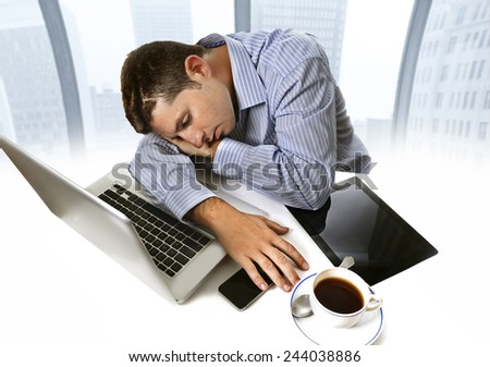 overworked businessman wearing blue shirt asleep at work tired and overloaded sitting with computer laptop, mobile phone and coffee cup in business district office - stock photo
