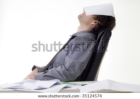Overworked businessman with pile of paperwork - stock photo