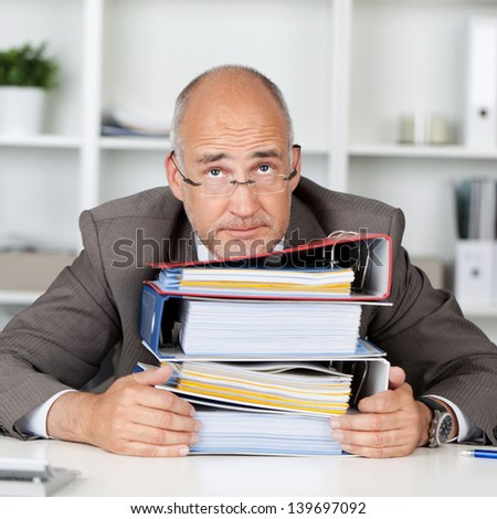overworked businessmann leaning head on a stack of binders - stock photo