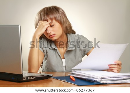 Overworked businesswoman isolated on grey - stock photo