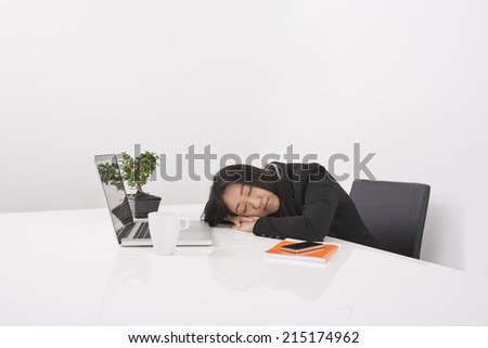 Overworked businesswoman resting at desk in office - stock photo