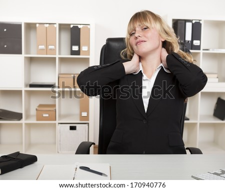 Overworked businesswoman stretching her neck as she sits at her desk in the office to relieve the strain of sitting all day - stock photo
