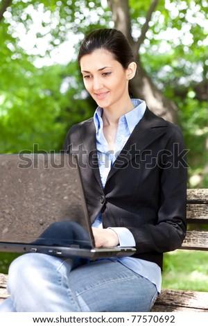 overworked businesswoman working on break in green park - stock photo