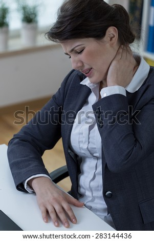 Overworked businesswomen suffer from neck pain - stock photo