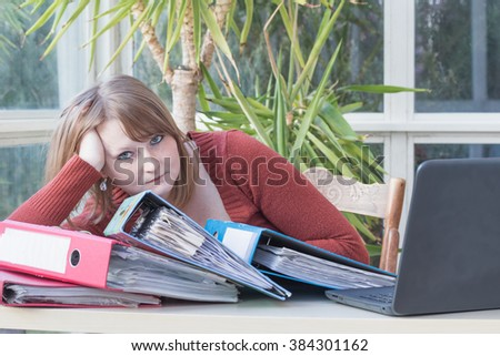 Overworked caucasian young woman is sitting at an office desk with her head propped on hand. Notebook and folders are lying against her. Green plant is in the background. All trademarks are removed. - stock photo