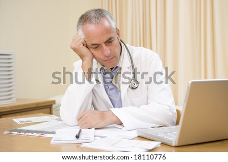 overworked doctor sat at desk - stock photo