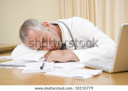 overworked doctor sleeping at desk - stock photo