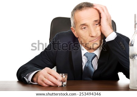 Overworked man drinking vodka in office. - stock photo