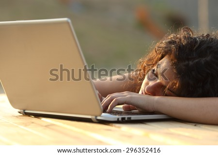 Overworked tired woman resting over a laptop in a park or a home table - stock photo