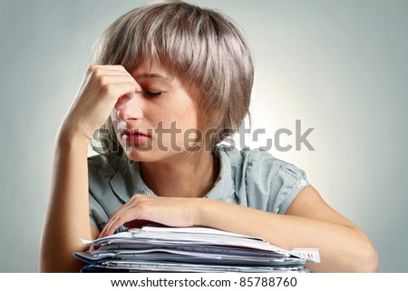 Overworked woman sitting at her working place isolated on grey - stock photo