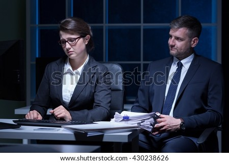 Overworked woman working at office at night and her boss with malignant smile - stock photo