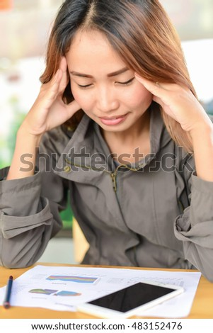 Overworked young woman sitting at the desk and holding his head