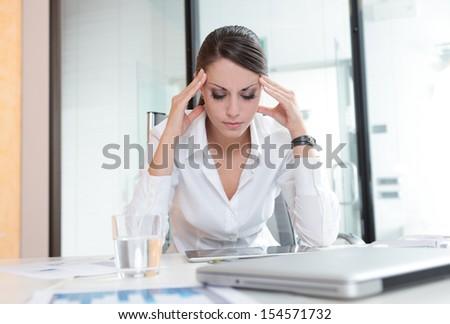 Overworking business woman suffering from headache  - stock photo