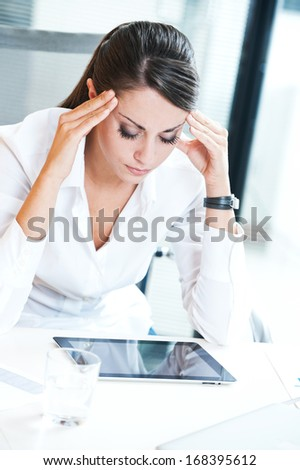 Overworking business woman suffering from headache