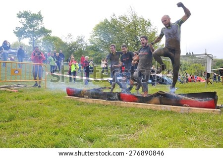 OVIEDO, SPAIN - MAY 9: Storm Race, an extreme obstacle course in May 9, 2015 in Oviedo, Spain. Runners jumping a barrier of fire. - stock photo