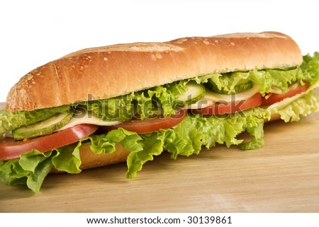 Ovo-lacto vegetarian sandwich containing: lettuce, tomato, cheese and zucchini. Selective focus on the left half. - stock photo