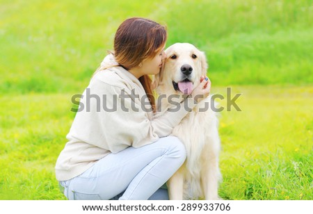 Owner and happy Golden Retriever dog together on the grass in sunny summer day