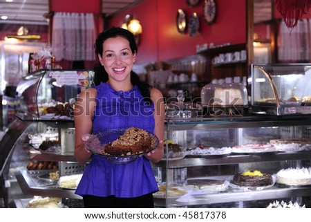 owner of a small business store showing her tasty cakes - stock photo