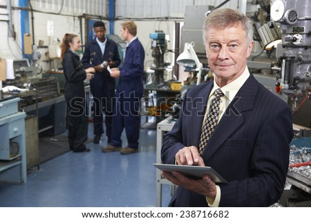 Owner Of Engineering Factory Using Digital Tablet With Staff In Background - stock photo